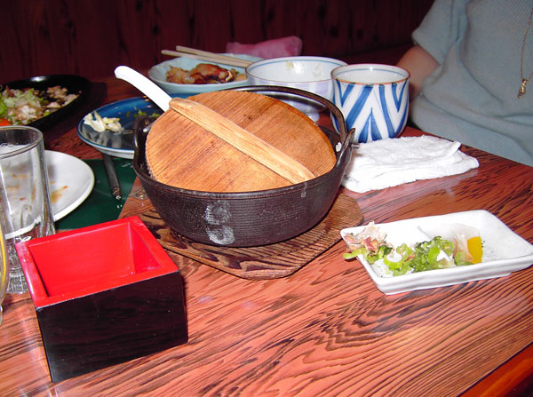 Red lacquered sake cup and iron pot of rice porridge